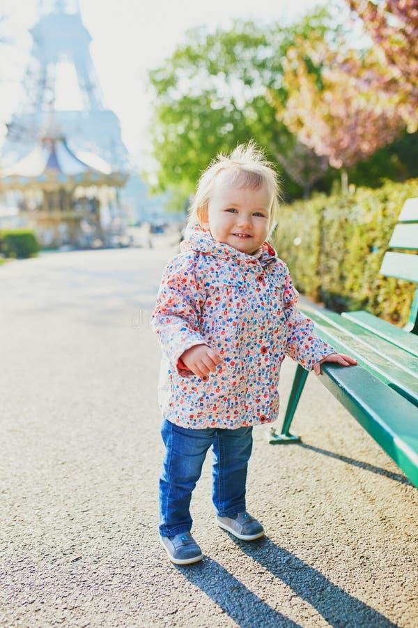 Годовалое положение девушки рядом со стендом в Париже, с Эйфелевой башней за ей стоковые изображения