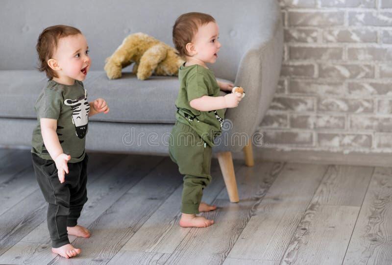 Годовалые двойные мальчики стоят около софы стоковые изображения