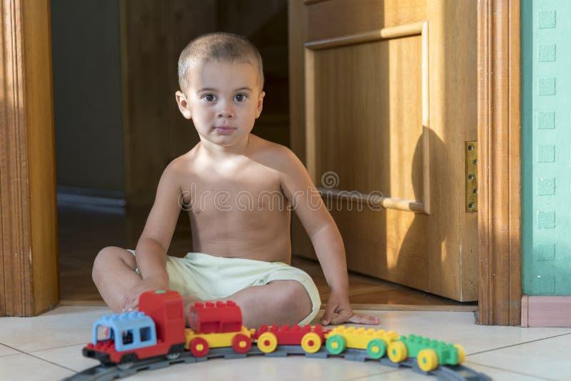 годовалый мальчик жизнерадостные 2 играя железную дорогу мальчик меньшяя локомотивная играя игрушка стоковые изображения rf