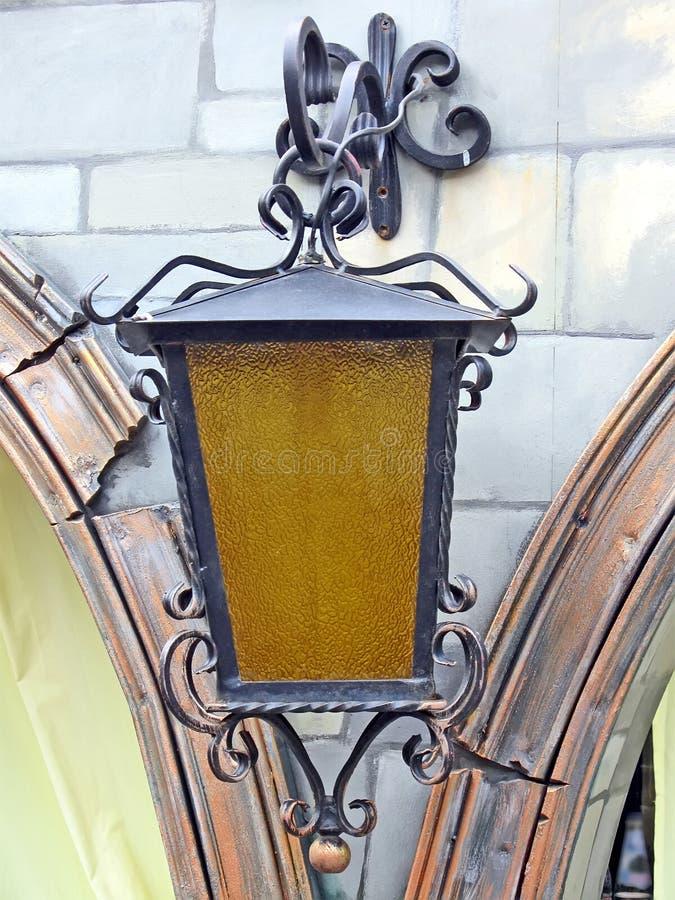 Год сбора винограда выковал медный уличный фонарь на стене, освещение металла силы ретро, стоковое фото