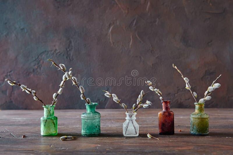 Год сбора винограда покрасил стеклянные бутылки с цветя ветвями вербы, дальше стоковое фото rf