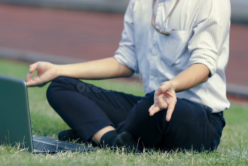 Год сбора винограда тонизировал изображение расслабленного молодого азиатского бизнесмена при компьтер-книжка делая положение йог стоковое изображение