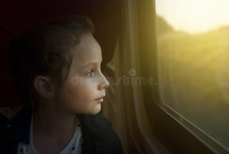 Год сбора винограда тонизировал mage маленькой девочки смотря через окно Она путешествует на железнодорожном поезде скопируйте ко стоковая фотография