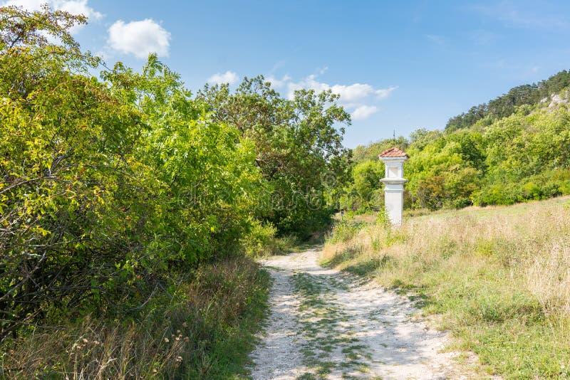 Голгофа около пути с деревьями и кустами лето голубого неба стоковые фотографии rf