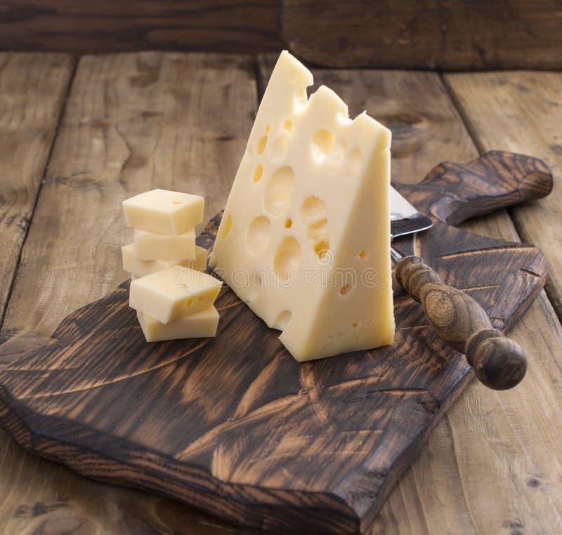 Голландский сыр с отверстиями на деревянной старой доске и сыр замешивают сбор винограда структуры фото абстрактной предпосылки о стоковая фотография rf