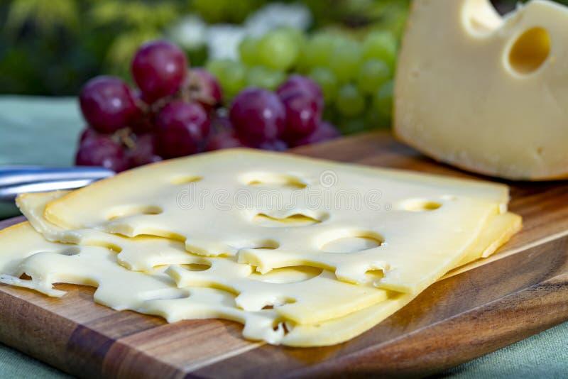 Голландский сыр с отверстиями, часть Maasdam трудный и отрезанный, служил на открытом воздухе в зеленом саде стоковые фотографии rf