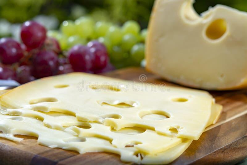Голландский сыр с отверстиями, часть Maasdam трудный и отрезанный, служил на открытом воздухе в зеленом саде стоковое фото rf