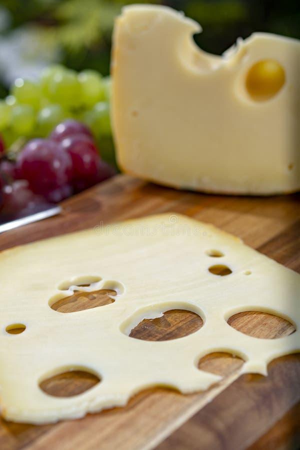 Голландский сыр с отверстиями, часть Maasdam трудный и отрезанный, служил на открытом воздухе в зеленом саде стоковые изображения rf