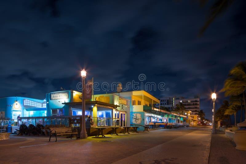 ГОЛЛИВУД, FL, США - 18-ОЕ ИЮЛЯ 2019: Фото ночи долгой выдержки пляжа Флориды Голливуд на полночи показывая закрытые рестораны стоковое фото rf