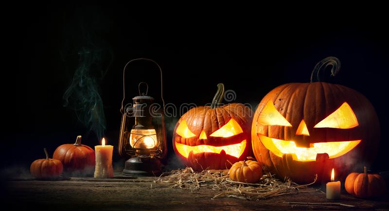 Голова тыквы хеллоуина поднимает фонарик домкратом с горящими свечами стоковые фото