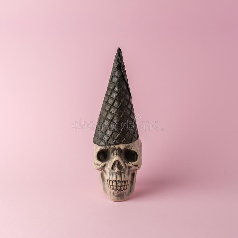 Голова черепа Хэллоуина с ведьмой шляпой из черного мороженого конуса на розовом фоне Минимальная концепция Хэллоуина стоковое фото