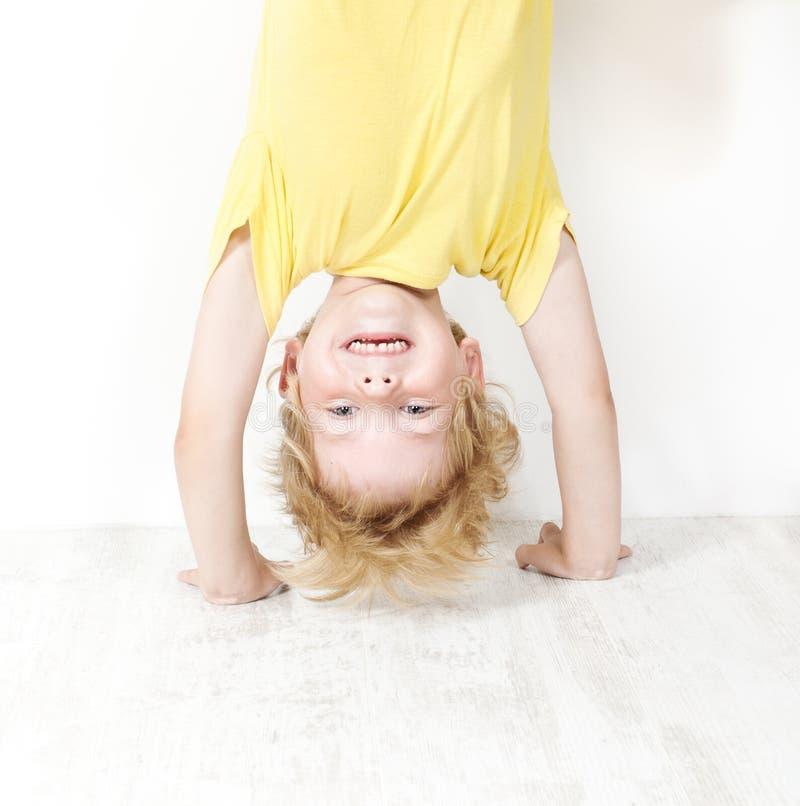 Головка смешного ребенка стоящая над пяткой стоковые фотографии rf