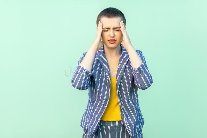 Головная боль или запутанность Портрет красивой красивой молодой женщины коротких волос в случайном striped положении костюма дер стоковое фото