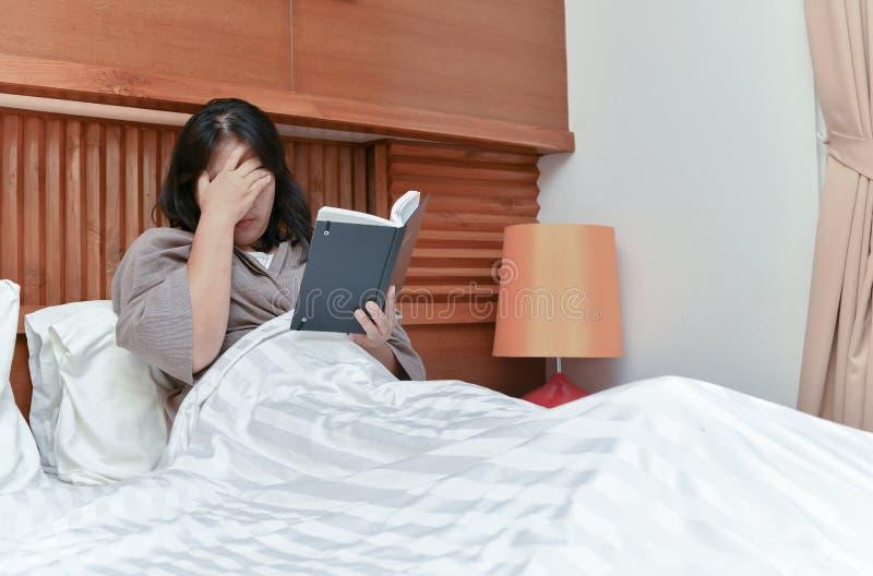 Головная боль полученная молодой женщиной прочитала книгу на кровати стоковая фотография