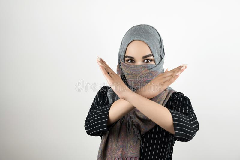 Головной платок hijab тюрбана молодого привлекательного мусульманского студента нося не говоря не к войне и насилию держит ее ору стоковая фотография