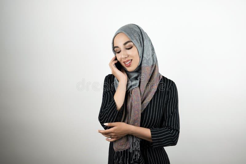 Головной платок hijab тюрбана молодой красивой счастливой мусульманской женщины нося говоря на предпосылке изолированной смартфон стоковое изображение