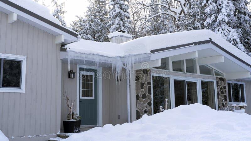 Головные боли зимы - запруда и сильный снегопад льда на крыше стоковая фотография