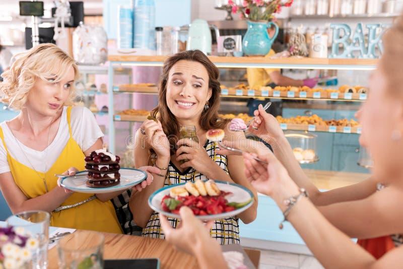 Голодная беременная женщина есть и соленья и десерт стоковое фото