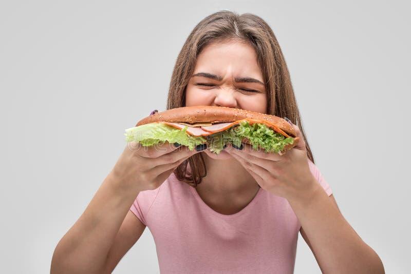 Голодный бургер укуса молодой женщины Она пожирает ее Изолировано на серой предпосылке стоковые изображения rf