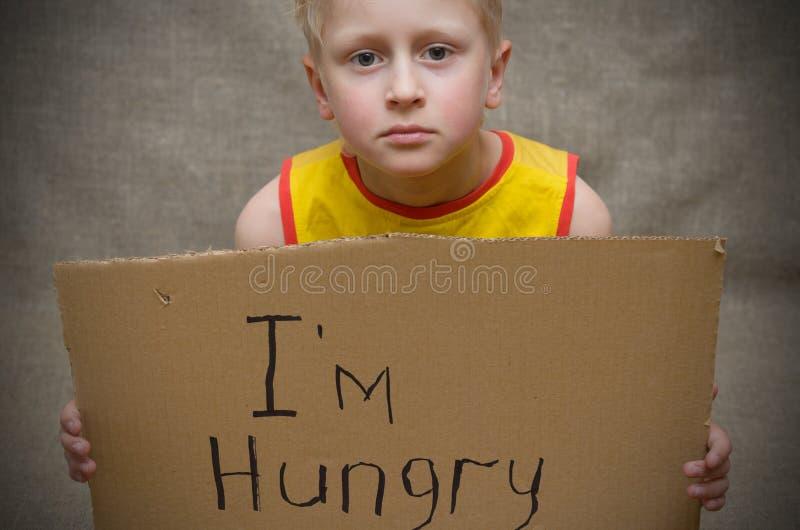 Голодный мальчик в желтой футболке с таблеткой картона с ` m надписи i голодным Социальная проблема стоковые фото