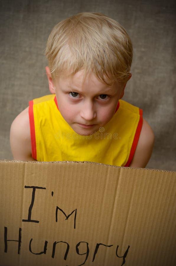 Голодный мальчик в желтой футболке с таблеткой картона с ` m надписи i голодным Социальная проблема стоковые фотографии rf