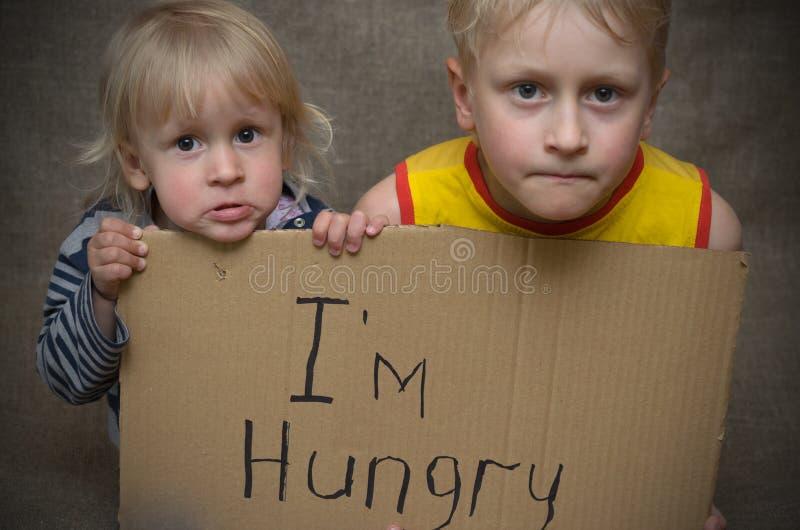 Голодный мальчик и девушка с таблеткой картона с ` m надписи i голодным Социальная проблема стоковое изображение