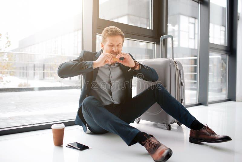 Голодный молодой человек пожирает бургер Он сидит на поле в аэропорте Стойка телефона на поле с чашкой кофе Чемодан там стоковое изображение