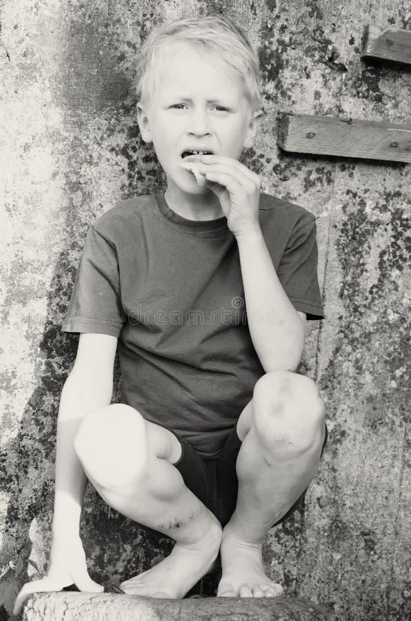 Голодный пакостный мальчик жадно ест корку хлеба против стены черная белизна стоковая фотография