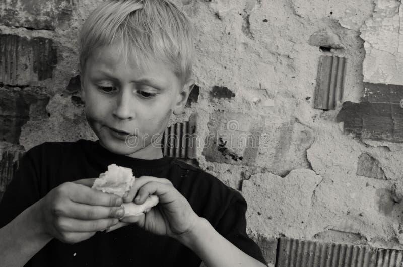 Голодный пакостный мальчик жадно ест корку хлеба против стены черная белизна стоковое фото rf