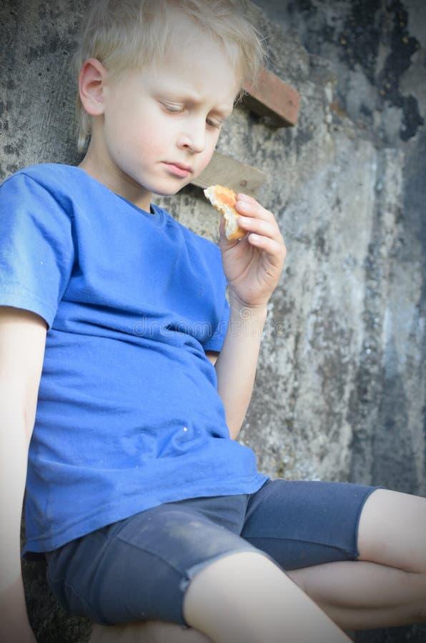 Голодный пакостный мальчик жадно ест корку хлеба против стены тонизировать стоковые изображения rf