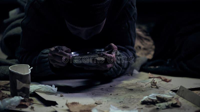 Голодный попрошайка есть от стального шара сидя на грязной коробке, прожитии улицы стоковое фото rf