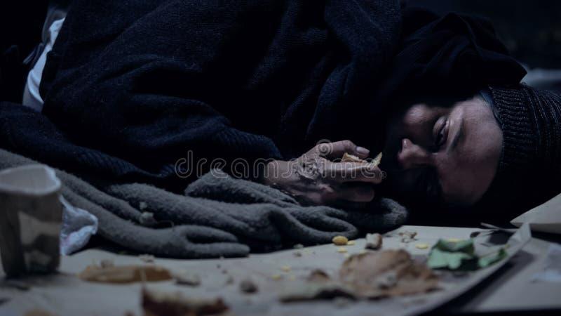 Голодный vagabond лежа на земле с отбросом и жадно есть orts, укрытие стоковые изображения