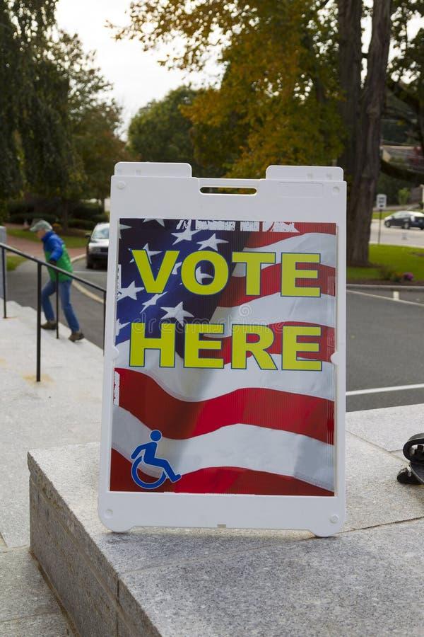 ГОЛОСОВАТЬ ЗДЕСЬ знак и избирателей стоковая фотография