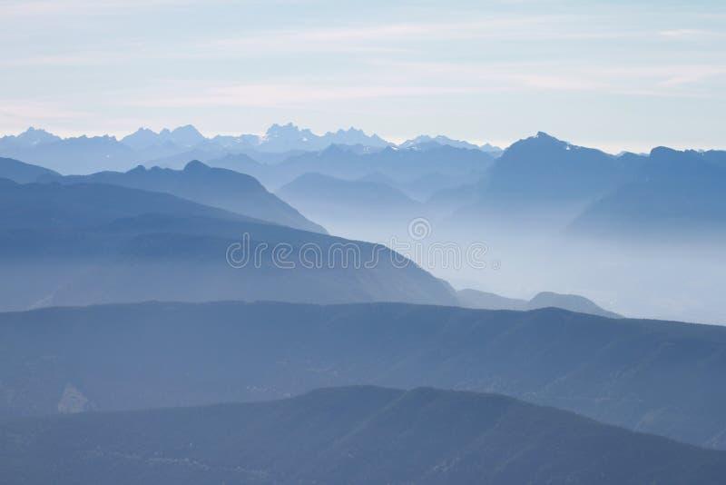Голубая горная цепь с пиками и долинами стоковое изображение