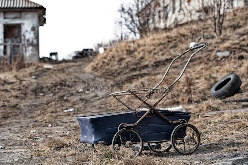 Голубая детская дорожная коляска на фоне получившейся отказ зоны апокалипсиса стоковые изображения