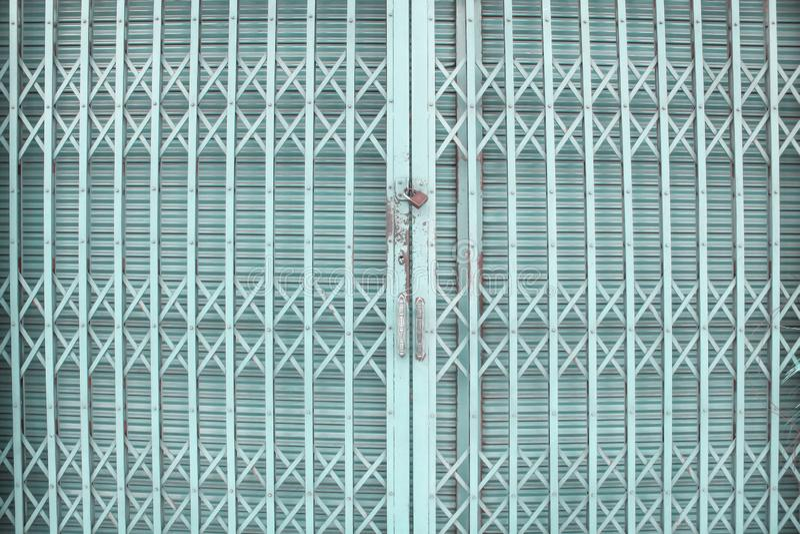 Голубая или зеленая свертывая стальная дверь или дверь шторки ролика внутри переплетают картины для предпосылки и ржавого заперто стоковые фото