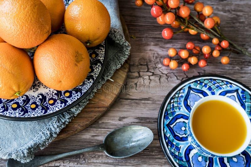 Голубая испанская handmade плита с апельсинами, соком и серебряной ложкой на деревянном столе стоковые фото