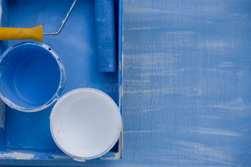 Голубая и белая краска во взгляде сверху консервных банок ролик с желтой ручкой для крася стен стоковые фотографии rf