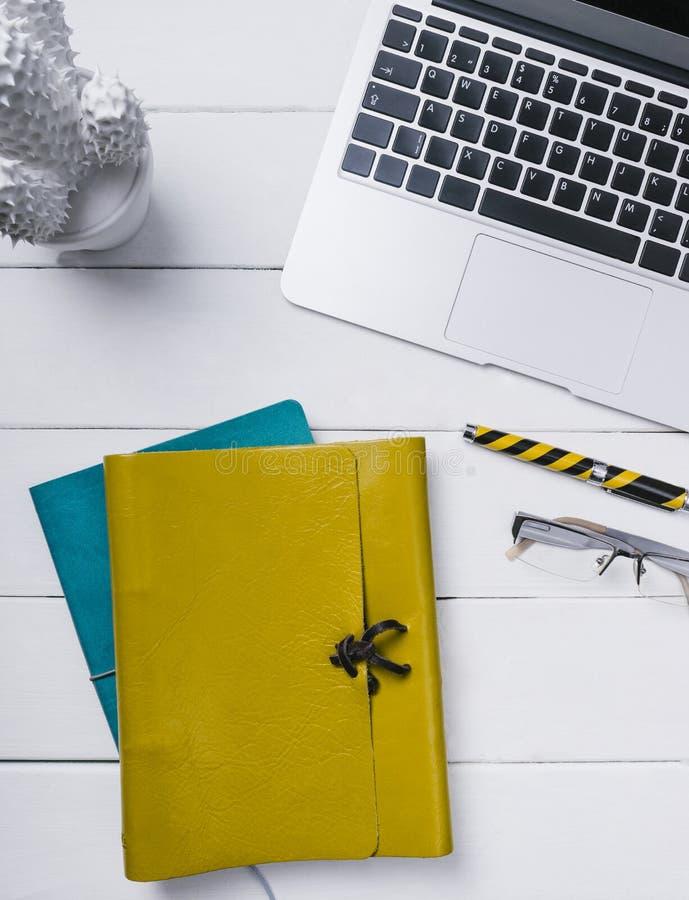 Голубая и желтая кожаная тетрадь, ручка, стекла и открытая тетрадь на белой предпосылке винтажной деревянной вертикали планок пок стоковые фотографии rf