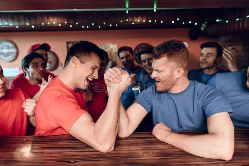 Голубая и красная команда дует армрестлинг на баре спорт с вентиляторами в предпосылке стоковое фото rf