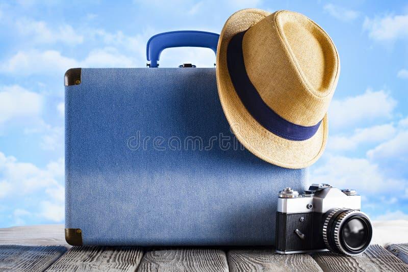 Голубая камера чемодана, шляпы лета и фото на деревянном столе и предпосылке песка пляжа стоковая фотография
