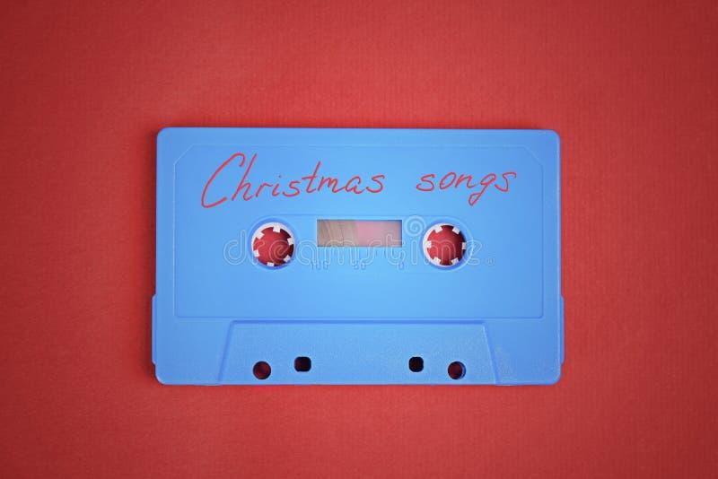 Голубая лента магнитофонной кассеты с песнями рождества кладя на красную бумажную предпосылку стоковое фото