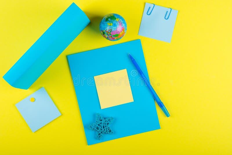 Голубая насмешка вверх по тетрадь и батту учебника для вопросов школы, глобуса и звезды ротанга на желтой предпосылке стоковое изображение rf
