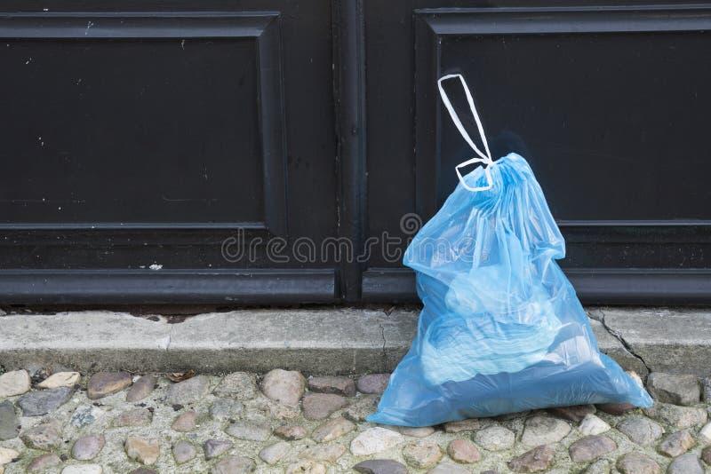 Голубая пластиковая сумка отброса перед дверью стоковые фото