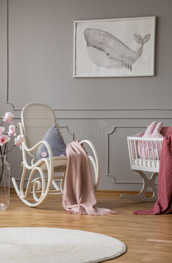 Голубая подушка и наклеить розовое одеяло на белой кресло-качалке в элегантной спальне комнаты младенца в арендуемом доме стоковое изображение rf