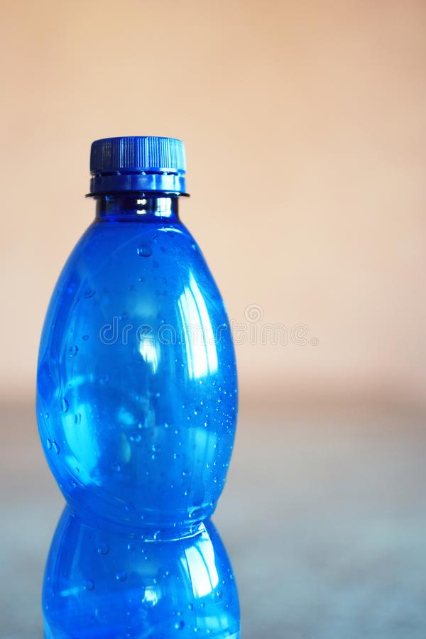 Голубая пустая пластичная бутылка с падениями пробочки и воды стоковые фото