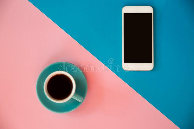 Голубая чашка с кофе и мобильным телефоном стоит на пинке и голубой предпосылке Завтрак утра, дело стоковые фотографии rf