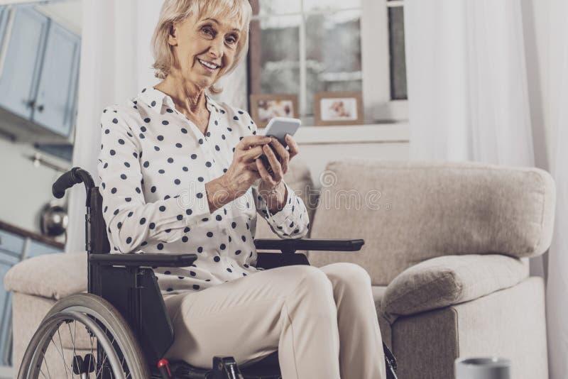 Голубоглазая женщина держа ее телефон сидя в кресло-коляске стоковое изображение rf