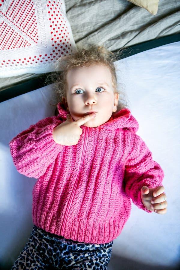 Голубоглазая милая девушка в розовом свитере думает стоковые изображения