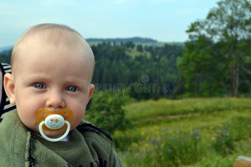 Голубоглазый младенец с pacifier внешним стоковое фото rf